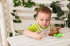 Gelukkig houdt weinig jong geitjejongen die zijn verjaardag vieren stuk van cake, binnen De partij van de verjaardag voor kindere Stock Foto