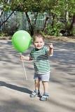 Gelukkig houdt weinig leuke jongen groene ballon en glimlacht Stock Foto