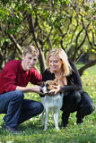 Gelukkig hurkend paar en aanrakingshond in park Royalty-vrije Stock Foto