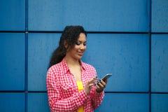 Gelukkig jeugdig meisje die via gadget bij de de zomertoevlucht communiceren stock foto