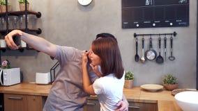 Gelukkig jong Aziatisch paar die smartphone voor selfie gebruiken terwijl thuis het koken in de keuken Man en vrouw die gezond vo stock videobeelden