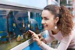 Gelukkig jong donkerbruin meisje die tropische vissen bekijken stock afbeelding