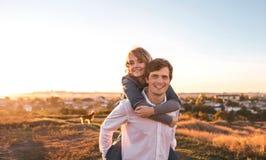 Gelukkig jong en paar die in openlucht koesteren lachen stock foto's