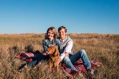 Gelukkig jong en paar die in openlucht koesteren lachen stock foto