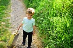 Gelukkig jong geitje in bloeiende aard Weinig jongenskind in groen bos Klein kind met stuk speelgoed in het winkelen zak De zomer royalty-vrije stock afbeelding