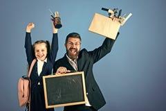 Gelukkig jong geitje die pret hebben Vader en schoolmeisje met gelukkige gezichten op blauwe achtergrond Stock Foto's