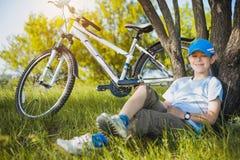 Gelukkig jong geitje met een fiets die onder een boom rusten stock fotografie