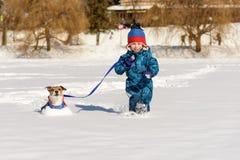 Gelukkig jong geitje met hond bij leiband het spelen op intacte verse sneeuw bij zonnige de winterdag stock afbeeldingen