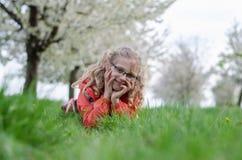Gelukkig jong geitje in tuinhoogtepunt van tot bloei komende bomen Stock Foto's