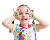 Gelukkig jong geitjemeisje die geschilderde handen met grappig tonen Royalty-vrije Stock Fotografie