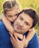 Gelukkig jong geitjemeisje die met liefde haar glimlachende vader op de zomer gr. koesteren stock afbeelding
