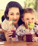 Gelukkig jong geitjemeisje en grappig emotioneel moeder het drinken bessen smoothie sap samen in straatkoffie close-up stock afbeelding