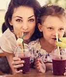 Gelukkig jong geitjemeisje en grappig emotioneel moeder het drinken bessen smoothie sap samen in straatkoffie close-up stock foto's