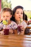 Gelukkig jong geitjemeisje en grappig emotioneel moeder het drinken bessen smoothie sap samen in straatkoffie close-up royalty-vrije stock afbeelding