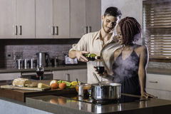 Gelukkig jong gemengd raspaar het drinken wijn kokend diner in keuken Stock Fotografie
