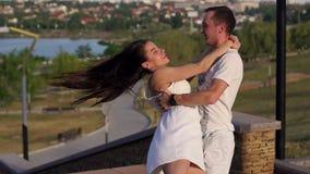 Gelukkig jong houdend van paar die een langzame wals bij zonsondergang in het park dansen stock videobeelden