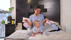 Gelukkig jong mamma die spelend met haar weinig babyzoon die in bed thuis liggen glimlachen stock footage