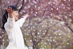 Gelukkig jong meisje die de bloemblaadjes van de kersenbloesem in de lucht buiten in een park in de lente werpen Stock Foto's