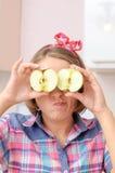 Gelukkig jong meisje die met twee appelen dichtbij haar ogen grappig gezicht maken Royalty-vrije Stock Foto's