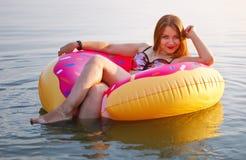 Gelukkig Jong meisje in een bestrooide doughnut stock afbeeldingen