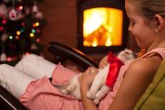 Gelukkig jong meisje met haar Kerstmisheden - een katje Stock Foto