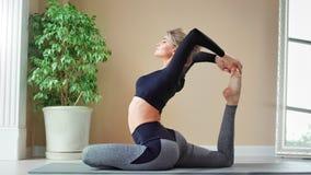 Gelukkig jong meisje met perfect flexibel lichaam die pilates training het opheffen been thuis van binnenland genieten stock footage