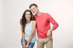 Gelukkig jong mooi zich en paar die verenigen lachen Studio die over witte achtergrond is ontsproten Vriendschap, liefde en stock foto's