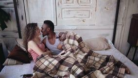Gelukkig jong multi-etnisch paar die onder deken, het koesteren en het kussen liggen Teder ochtend van de mens en vrouw op het be stock foto