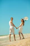 Gelukkig jong paar dat pret op het strand heeft stock fotografie