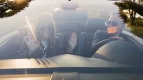 Gelukkig jong paar die in cabriolet dansen stock videobeelden