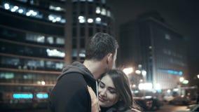 Gelukkig jong paar die in de avond koesteren stad stock videobeelden