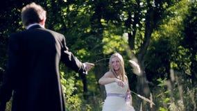 Gelukkig jong paar die in de de zomertuin lopen stock footage