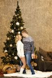Gelukkig jong paar die door de Kerstboom dansen Stock Afbeeldingen