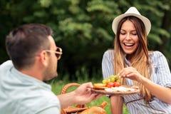 Gelukkig jong paar die een grote tijd op een picknick in een park hebben stock foto