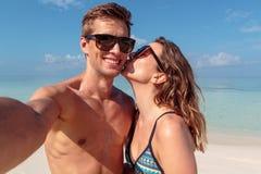 Gelukkig jong paar die een selfie, duidelijk blauw water als achtergrond nemen Meisje die zijn vriend kussen royalty-vrije stock foto's
