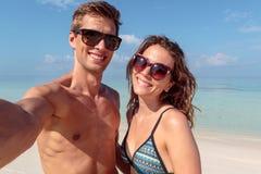 Gelukkig jong paar die een selfie, duidelijk blauw water als achtergrond nemen omhelzing stock afbeelding
