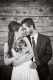 Gelukkig jong paar die in huwelijksdag bij elkaar glimlachen Stock Fotografie