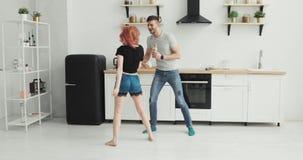 Gelukkig jong paar die in keuken dansen die pyjama's dragen die aan muziekochtend thuis luisteren stock videobeelden