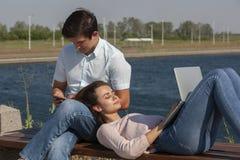 gelukkig jong paar die laptop met behulp van terwijl het zitten samen in park royalty-vrije stock afbeelding
