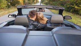 Gelukkig jong paar die in liefde terwijl het drijven van cabriolet koesteren stock videobeelden