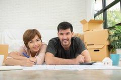 Gelukkig jong paar die met blauwdrukken hun nieuw huis plannen royalty-vrije stock afbeeldingen
