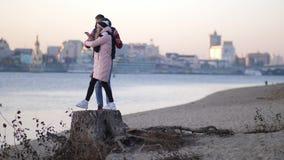 Gelukkig jong paar die op het strand in de herfst tegen de achtergrond van de rivier lopen die op de stomp worden die glimlachen  stock footage