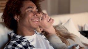 Gelukkig jong paar die op TV letten samen terwijl thuis het zitten op bank stock footage