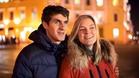 Gelukkig jong paar die pret in de nachtstad hebben stock videobeelden