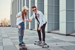 Gelukkig jong paar die pret hebben terwijl het drijven op een moderne straat met een skateboard rijdt stock foto