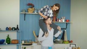 Gelukkig jong paar die pret in keuken hebben thuis Het meisje zit op vriend` s hals stock videobeelden