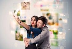 Gelukkig jong paar die selfie beelden nemen stock foto's