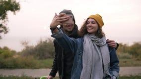 Gelukkig jong paar die selfie door mobiele telefoon in de herfstpark nemen Meisje die in gele hoed smartphone houden Mooi stock footage