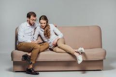 Gelukkig jong paar die smartphone gebruiken samen terwijl het zitten op bank Royalty-vrije Stock Foto's