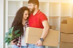 Gelukkig jong paar die of verpakkingsdozen en het bewegen zich in a uitpakken royalty-vrije stock afbeeldingen